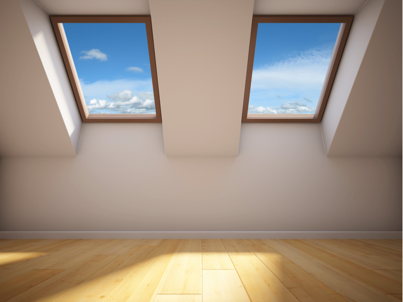 Empty new room with fixed skylights against blue cloudy skies