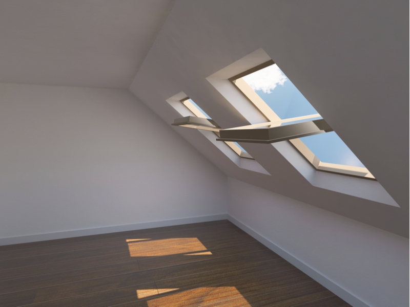 Empty new room with ventilated skylights against blue cloudy skies